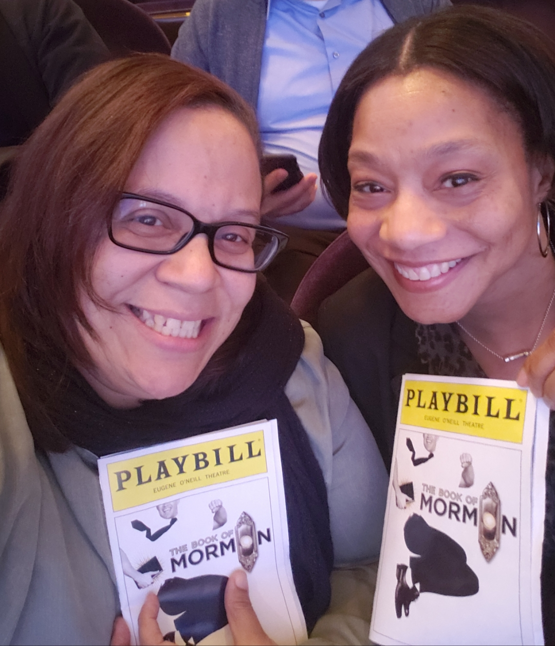 A close-up photo of two women holding playbills for The Book of Mormon and smiling.